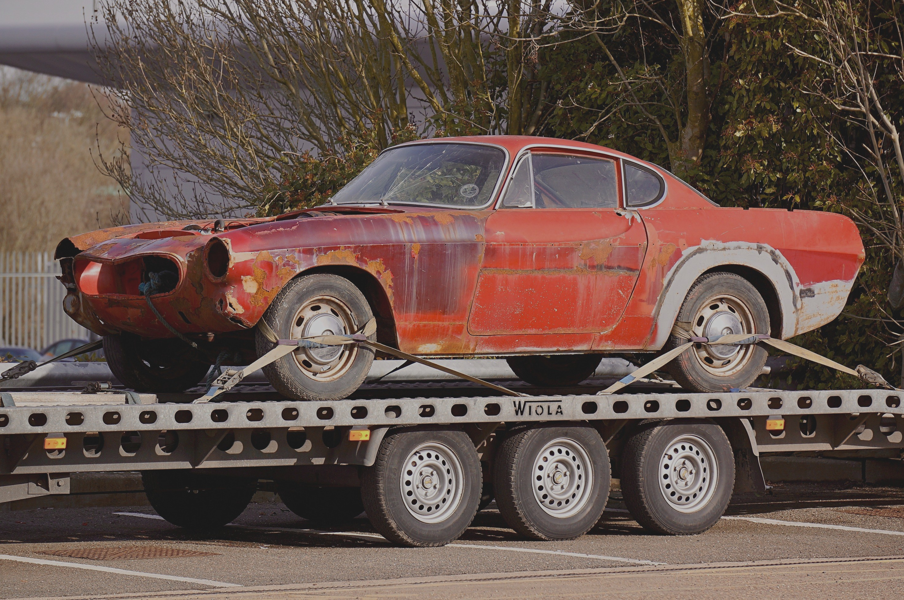antique muscle car on flatbed tow truck